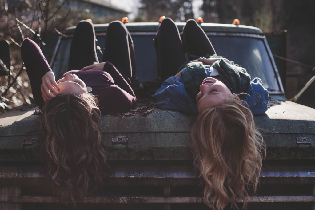 two girls chatting on a car